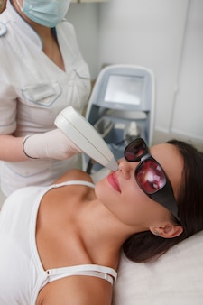Foto vertical de uma mulher fazendo depilação a laser do lábio superior na clínica de cosmetologia