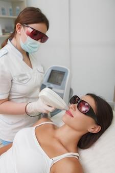 Foto vertical de uma mulher fazendo uma depilação a laser no lábio superior