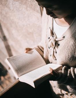Foto vertical de uma mulher lendo um livro