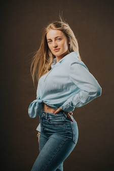 Foto vertical de uma mulher loira atraente em jeans e uma camisa curta posando em um fundo marrom