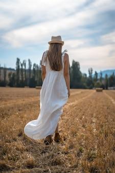 Foto vertical de uma mulher loira atraente em um vestido branco andando em um campo