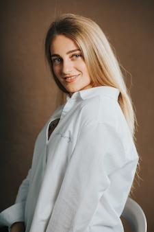 Foto vertical de uma mulher loira atraente em uma camisa branca, posando em uma parede marrom