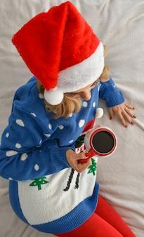 Foto vertical de uma mulher loira caucasiana vestindo roupas de natal e bebendo café