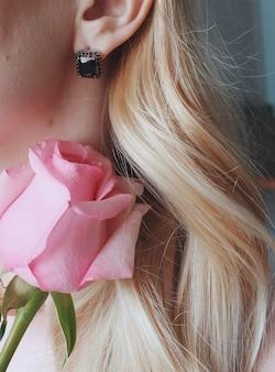 Foto vertical de uma mulher loira usando um brinco com uma pérola negra segurando uma rosa