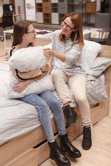 Foto vertical de uma mulher madura conversando com sua filha adolescente enquanto comprava móveis de quarto em uma loja de artigos para casa