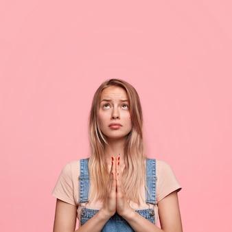 Foto vertical de uma mulher miserável e atraente mantendo as palmas das mãos juntas
