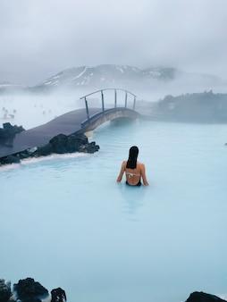 Foto vertical de uma mulher nadando em uma piscina aquecida perto da ponte