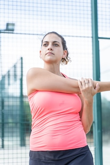 Foto vertical de uma mulher no sportswear, esticando os braços em uma quadra de tênis
