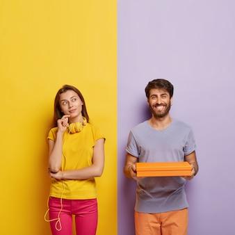Foto vertical de uma mulher pensativa em pose pensativa, pensa em algo, usa fones de ouvido no pescoço, usa camiseta amarela e calça rosa, homem alegre segura uma caixa de papelão nas mãos