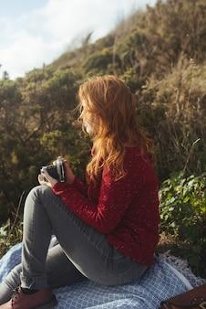 Foto vertical de uma mulher sentada em um cobertor com as árvores e o mar