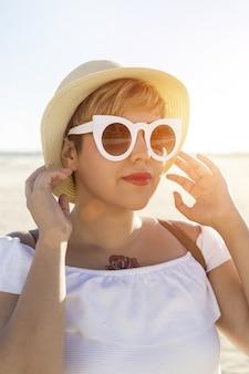 Foto vertical de uma mulher usando óculos escuros brancos e um chapéu, capturada na praia