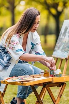 Foto vertical de uma mulher usando potes de tinta na frente de uma tela em um parque.