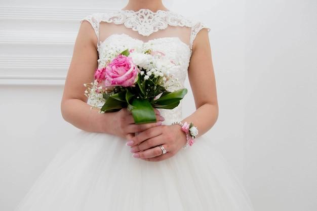 Foto vertical de uma noiva segurando um buquê de flores coloridas