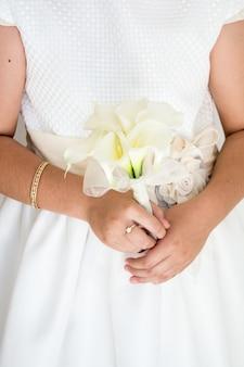 Foto vertical de uma noiva segurando um lindo buquê de flores brancas