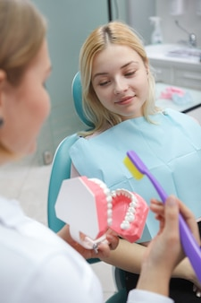 Foto vertical de uma paciente sentada na cadeira odontológica falando com seu dentista