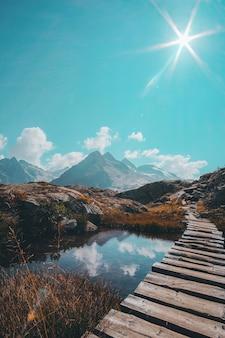 Foto vertical de uma passagem de madeira sobre um pequeno lago reflexivo e uma cadeia de montanhas no horizonte