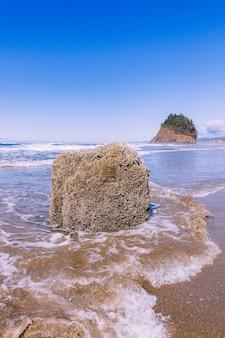 Foto vertical de uma pedra no oceano sob um céu azul claro