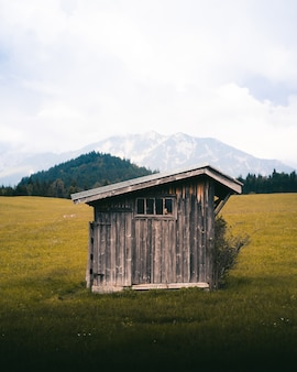 Foto vertical de uma pequena casa de madeira em um campo aberto com altas montanhas