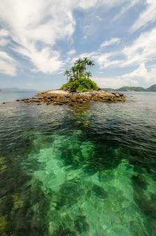Foto vertical de uma pequena ilha no mar cristalino sob um céu azul