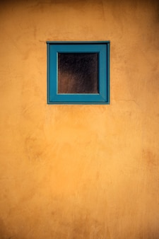 Foto vertical de uma pequena janela azul em uma porta de madeira