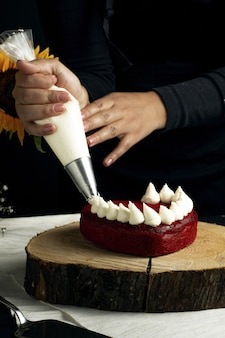 Foto vertical de uma pessoa adicionando creme branco em um bolo de veludo vermelho chique em forma de coração