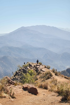 Foto vertical de uma pessoa caminhando de volta da borda de uma montanha ao longe