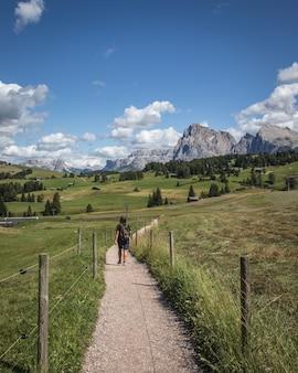 Foto vertical de uma pessoa caminhando em um caminho de terra com a montanha plattkofel