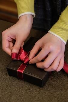 Foto vertical de uma pessoa embrulhando um presente com uma linda fita vermelha