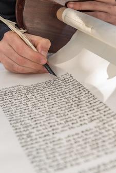 Foto vertical de uma pessoa escrevendo com uma pena em um pergaminho