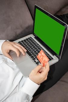 Foto vertical de uma pessoa inserindo detalhes de seu cartão de crédito no laptop