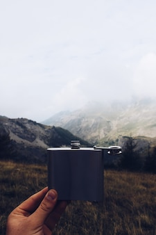 Foto vertical de uma pessoa segurando um frasco de metal com uma montanha e o céu nublado