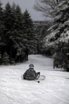 Foto vertical de uma pessoa sentada na colina usando uma prancha de snowboard