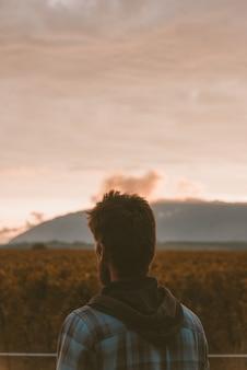 Foto vertical de uma pessoa solitária apreciando a bela vista do pôr do sol