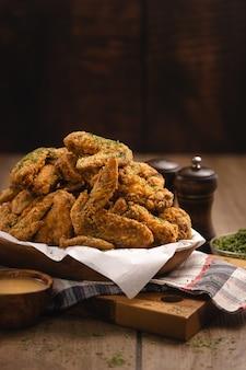 Foto vertical de uma pilha de asas de frango frito e alguns temperos em uma mesa de madeira