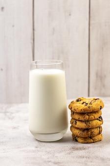 Foto vertical de uma pilha de biscoitos de chocolate ao lado de um copo de leite em uma mesa