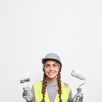 Foto vertical de uma pintora profissional segurando um pincel e um rolo com um sorriso alegre