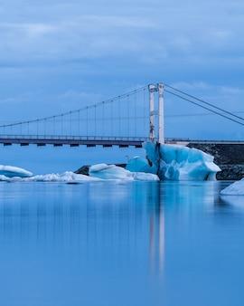 Foto vertical de uma ponte na lagoa da geleira jokulsarlon, na islândia