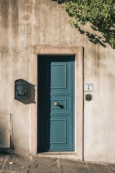 Foto vertical de uma porta azul bonita em um prédio de pedra