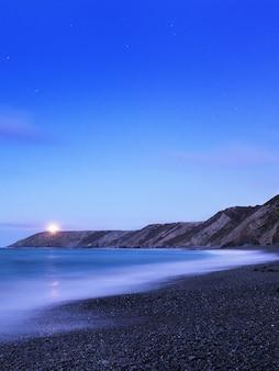 Foto vertical de uma praia com uma montanha e um pôr do sol que está quase no fim