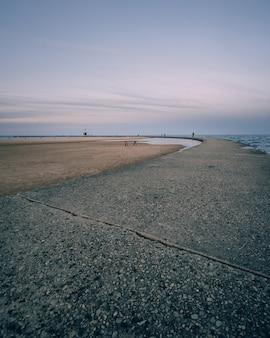 Foto vertical de uma praia vazia e um céu azul claro