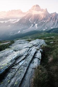 Foto vertical de uma rocha em uma colina gramada com montanhas