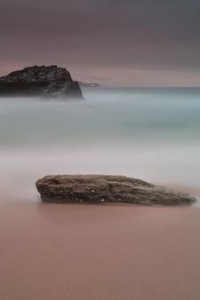 Foto vertical de uma rocha na costa sob o céu roxo escuro