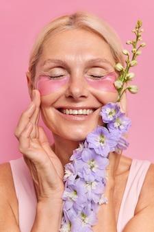 Foto vertical de uma senhora madura de cabelos louros sorrindo amplamente mostra dentes brancos tocando o rosto suavemente aprecia a suavidade da pele aplica adesivos de hidrogel sob os olhos segura flor passa por procedimentos de beleza