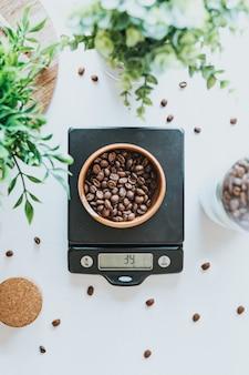 Foto vertical de uma tigela cheia de grãos de café em escala digital preta de 39 gramas
