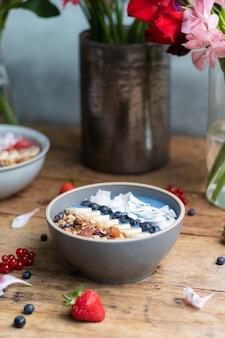 Foto vertical de uma tigela de smoothie de mirtilo saudável com frutas e granola