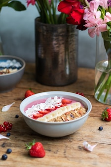 Foto vertical de uma tigela de smoothie saudável com frutas e granola