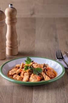 Foto vertical de uma tigela de sopa de frango e legumes e alguns temperos em uma superfície de madeira