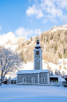 Foto vertical de uma torre de relógio com montanhas cobertas de neve