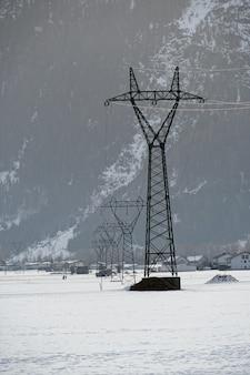 Foto vertical de uma torre de transmissão com uma superfície de neve durante o inverno