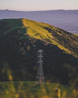 Foto vertical de uma torre elétrica em uma montanha gramada
